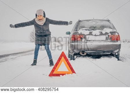 Young Woman Stands By Her Car, Arms And Legs Spread Apart, Screaming, Angry, And Waiting For Help. C