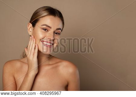Beauty Young Woman Touches Her Face With Her Hands. Young Pretty Lady With Natural Makeup On Beige B
