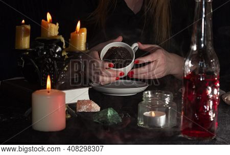 Fortune-telling On Coffee Grounds. A Fortune Teller's Hands, A Cup Of Coffee, Candles, And Skulls On