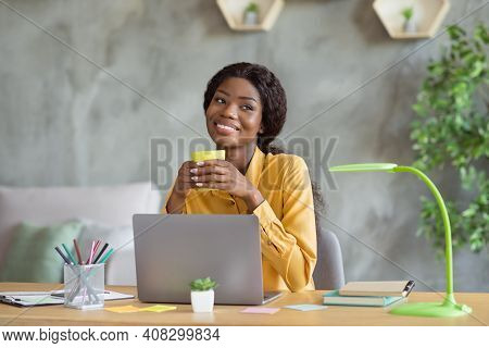 Photo Of Happy Dreamy Dark Skin Young Business Woman Sit Office Desk Relax Drink Coffee Job Indoors
