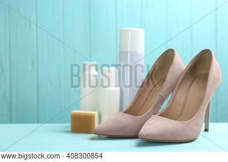 Stylish Footwear With Shoe Care Accessories On Light Blue Wooden Table