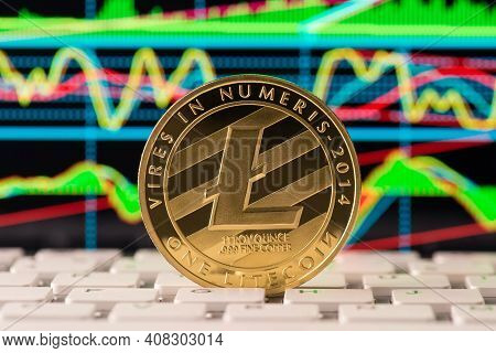 Close Up Photo Of Golden Shining Lite Coin Standing On The White Keyboard With Colorful Diagrams On