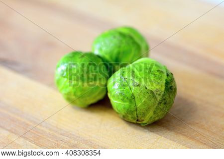 Group Of Three Whole Fresh Brussels Sprouts On Wooden Plate.