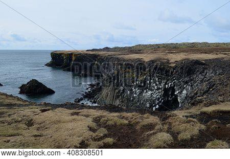 Amazing Black Rock Cliffs With Basalt Columns On The Coastline.