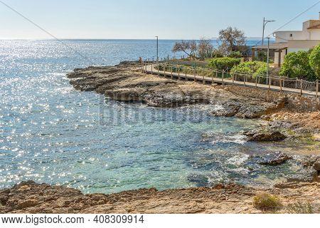 Colonia De Sant Jordi Promenade On A Sunny And Winding Day. Mediterranean Sea In The Rocky Coast Of