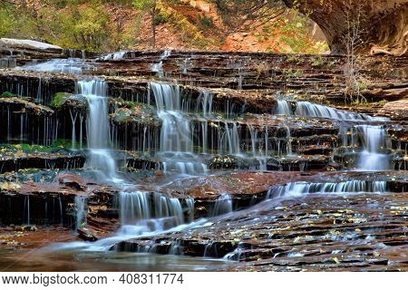 Terraced waterfalls with fall color along the Left Fork of North Creek in the Subway section of Zion National Park, Utah