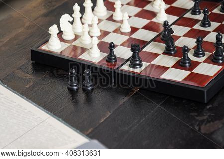 Close-up Of Chess Pieces Placed On Chessboard At Beginning Of The Game And Stack Of Old Books. Conce