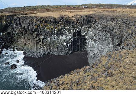 Tall Cliffs Made Of Rock Basalt Columns And A Black Sand Beach.