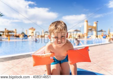 Kid With Inflatable Armbands Near Swimming Pool. Little Boy Learning To Swim In Outdoor Pool Of Trop