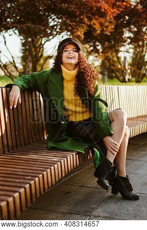 A Girl Sitting In The Park Threw Her Foot On Her Leg And Gleefully Laughs By Throwing Her Head Up. H