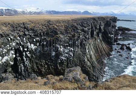 Stunning View Of Rock Cliffs, Basalt Columns And Snow Covered Mountains.