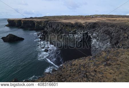 Iceland's Rock Cliffs With Basalt Columns Along The Rugged Coast.