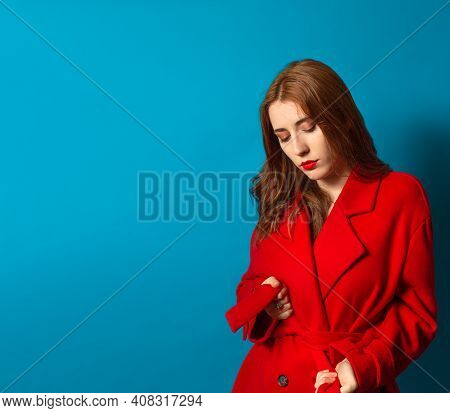 Woman With Make-up And Red Lips Wearing Her Red Trench Coat On A Blue Background And With Blank Spac