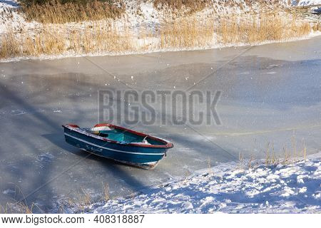 Frozen Ditch With Wooden Rowing-boat Lying On The Ice