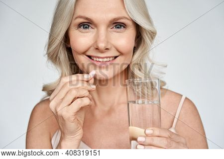 Smiling Happy Healthy Middle Aged 50s Woman Holding Glass Of Water Taking Dietary Supplement Vitamin