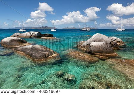 Boulders dot the waters of the Baths with boats moored in the distance at the Baths on Virgin Gorda in the British Virgin Islands.