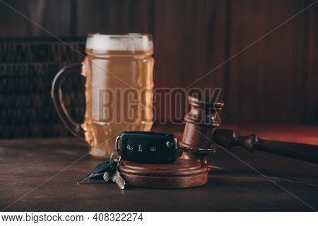 Glass Of Beer, Car Keys And Judge Gavel On A Wooden Table. Alcohol And Driving Ability