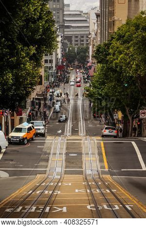 A Vertical Shot Of A Street Sloping Downwards In The Busy City Of San Francisco, California, United