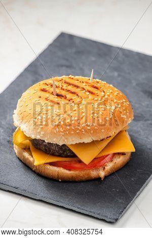 still life of cheeseburger on black plate