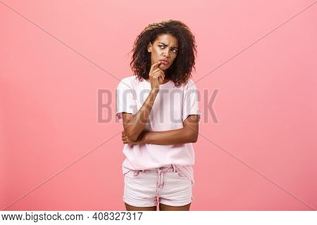 Displeased Dark-skinned Young Curly-haired Woman In Trendy T-shirt And Shorts Saying Hmm Touching Ch