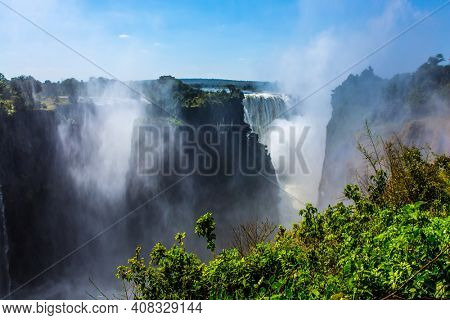 Giant cloud of water fog over the waterfall Victoria Falls. Journey after the wet season. The waterfall is located on the Zambezi River. Concept of extreme and photo tourism