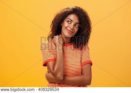 Cute And Gentle Dreamy Dark-skinned Girl With Cruly Hairstyle Tilting Head Smiling From Delight And