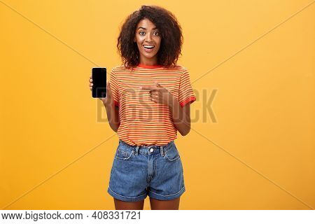 Cute African American Stylish Woman Showing Friend New App In Smartphone Pointing At Cellphone Scree