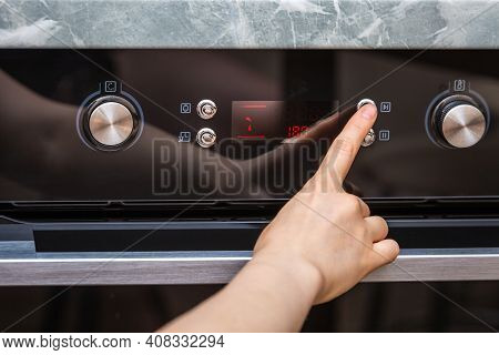 Female Hand Turning On The Oven To Make A Cake At Home. Close-up Of The Oven Knob. View Of The Black