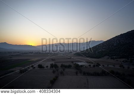 Breathtaking View Of Sunrise Over Foggy Mountains. Valley With Fields And Meadows In The Early Morni