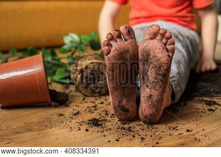Kid Sitting On The Floor Of The Room With Dirty Feet. Inverting Flowerpot. Concept Of Failure. High