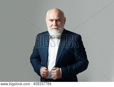 Closeup Portrait Of Senior Man With Grey Hair Isolated On Gray Background. Old Man. Waist Up Portrai