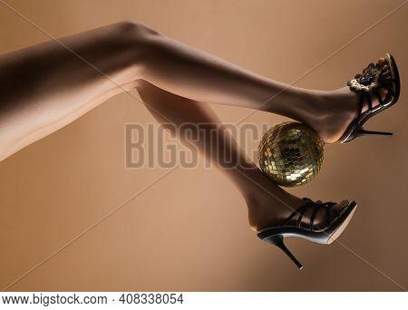 Sexy Legs. Disco Party. Woman Legs With Gold Disco Ball. Celebrate Concept. Gold Disco Ball On High