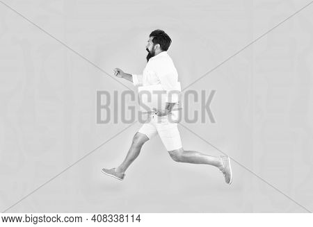 Running Into Busy Life. Busy Man In Midair Yellow Background. Energetic Hipster Run With Laptop Pc.