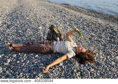 Young Woman Hiker Lies Serenely On Deserted Pebble Shore. She Holds Bouquet Of Wildflowers In Her Ha