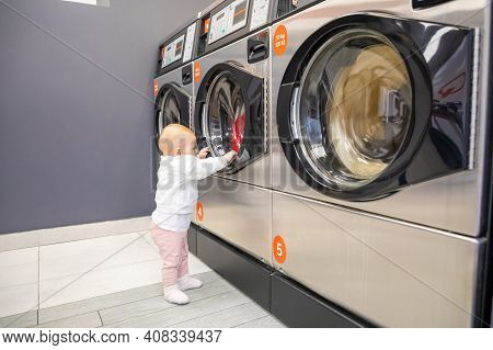 Prague, Czech Republic - 16.12.2020: Baby Girl Waiting For Laundry In Laundry Room With Speed Queen
