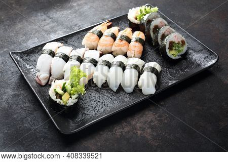 A Sushi Set. Nigiri And Futomaki With Shrimps, Butterfish And Calabash On A Black Stony Background.