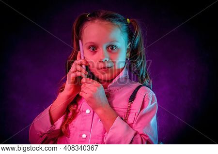 The Little Girl Is Talking On The Phone. A Surprised, Startled Face. Studio, Neon Light, Gel Filters