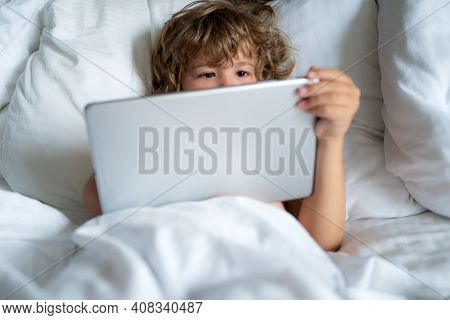 Social And Technology Concept. Kids Internet. Child With Tablet In Bed. Parental Permission, Safety
