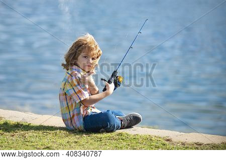 Child Fishing On The Lake. Young Fisher. Boy With Spinner At River. Portrait Of Excited Boy Fishing.
