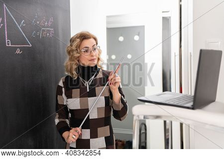 Young Female Math Teacher Explaining Geometry On The Black Wall. Chair On The Table And Laptop On Th