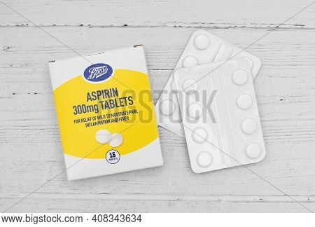London / Uk - February 15th 2021 - Aspirin Packet And Tablets On A Wooden Table, 300mg Tablets From