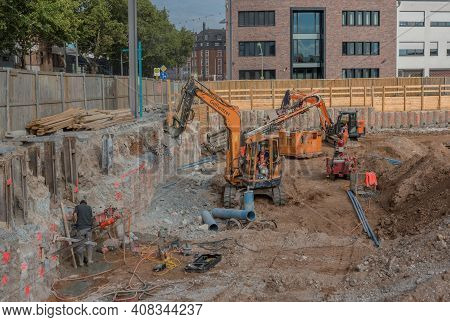 Worker In The Foundation Trench With Construction Machinery On The Construction Site
