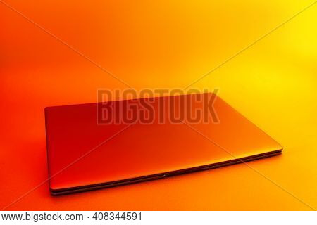 Slim Modern Laptop With White Screen Mockup Set Against Bright, Red Creative Light.