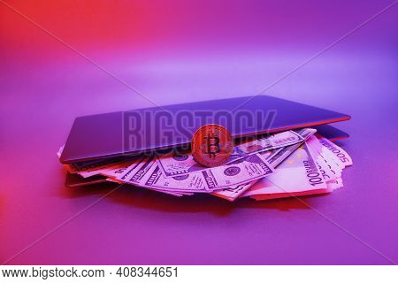 Laptop With Cryptocurrency Bitcoin And Bundles Of Dollars And Euros Against A Background Of Colorful