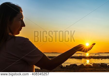 Beautiful Woman Holding Sun In Her Hand Or Palm, Witch Trough Shines Sunstar With Sunrays At Beautif