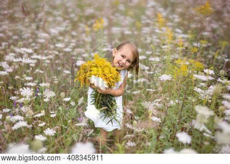 Little Girl With A Bouquet Of Goldenrod Flowers In A Large Field Of Blooming Achillea Millefolium. A