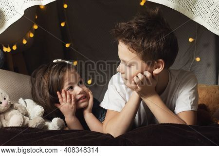Siblings Lie In A Hut Of Chairs And Blankets. Brother And Sister Smiling Playing At Home