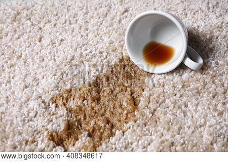 Overturned Cup And Spilled Tea On Beige Carpet, Closeup