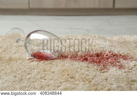 Overturned Glass And Spilled Red Wine On Soft Carpet