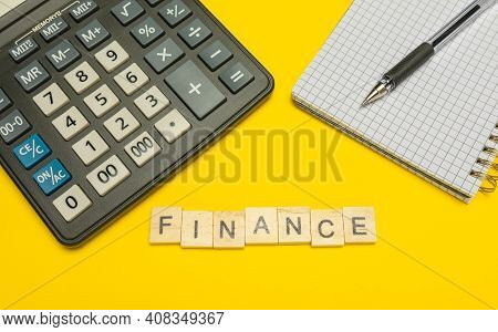 Word Finance Made With Wood Letters On Yellow Background And Modern Calculator With Pen And Notebook